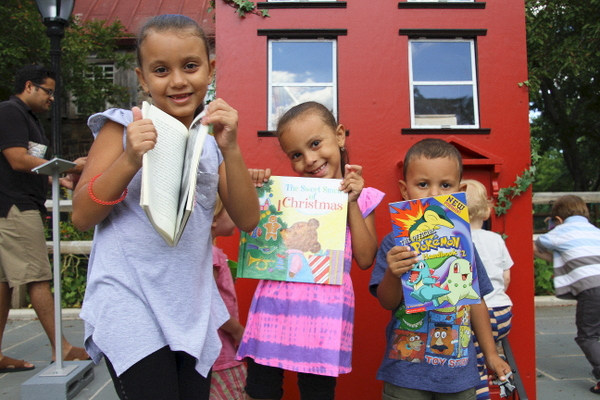 Local children show off their favorite books (photo by Becki Fuller, © Leon Reid IV)